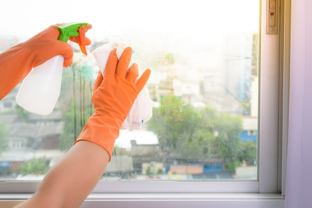 Hand in gloves cleaning window with rag and cleanser spray at home.