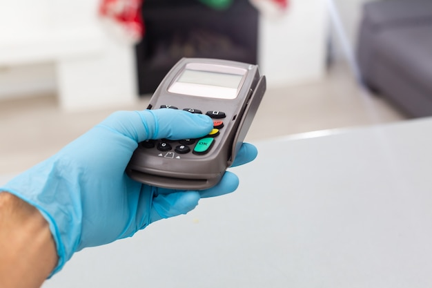 Hand in gloves and pos terminal, successful contactless payment.