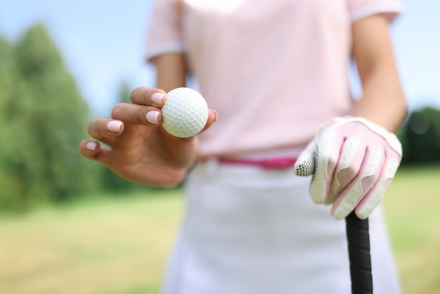 In hand of golf ball second gloved hand holds golf club.
