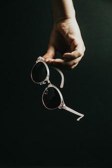어두운 배경, 스타일 및 최소한의 개념, 우아함, 여름 휴가 위에 어두운 선글라스 한 쌍을 손으로 움켜쥔다