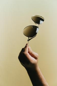 파스텔 노란색 배경, 스타일 및 최소한의 개념, 우아함, 여름 휴가 위에 어두운 선글라스 한 쌍을 손으로 잡으십시오.