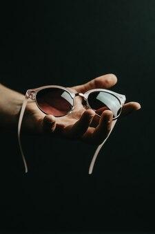어두운 배경, 스타일, 최소한의 개념, 우아함, 여름 휴가 위에 분홍색 선글라스 한 켤레를 손으로 잡아라