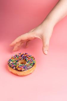 ピンクの背景に振りかけるとチョコレートのフロストドーナツをつかむ手。