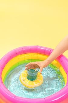 Рука схватила стекло, плавающее в надувной лодке в красочном небольшом бассейне на желтом фоне