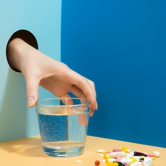 Hand grabbing glass of water with pills next to it