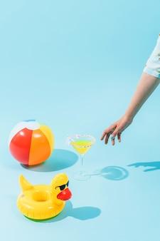 Рука хватает желтый стакан для напитков, пляжный мяч и пластиковую надувную утку на голубом фоне