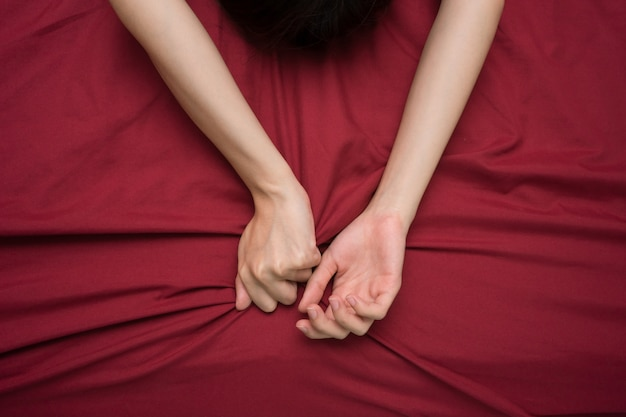 Hand grasping on bed sheet Premium Photo