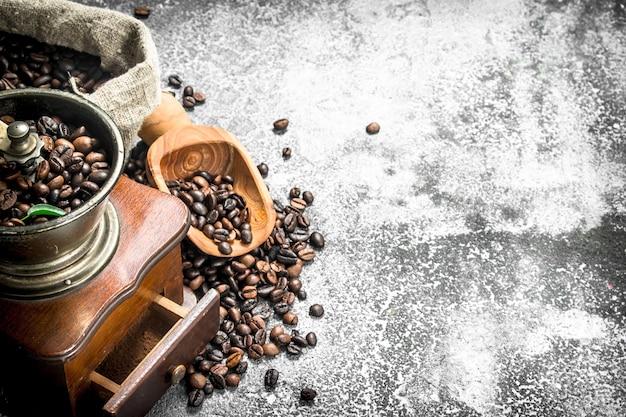 コーヒー豆とハンドグラインダー。素朴なテーブルの上。