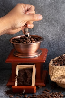 Hand grinding coffee beans in wooden grinder