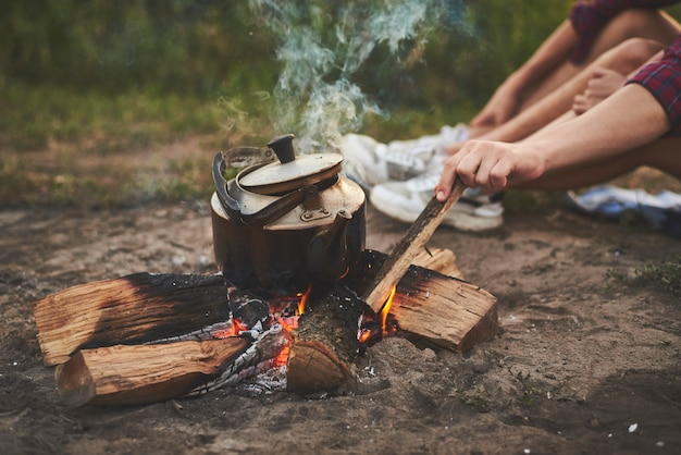 The hand of a guy fixes a fire with a stick on which the kettle is boiling