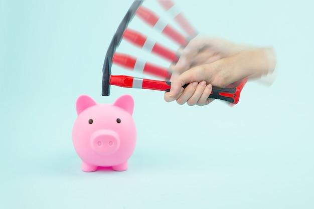 손 망치는 저축으로 돼지 저금통을 부수고 있습니다. 금융 위기의 개념입니다.