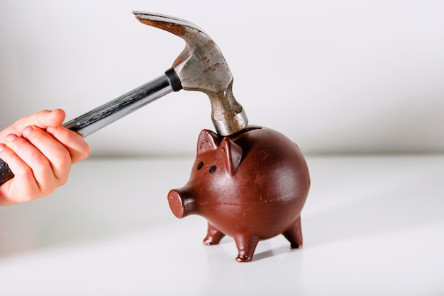 Hand hammers a piggy bank, isolated on white