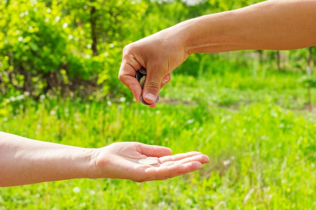 Hand in hand gives coins on green background, finance concept and loans.