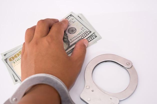 Hand in handcuffs holding dollar bills. man handcuffed with bribe