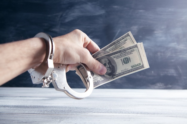 Hand in handcuffs holding money