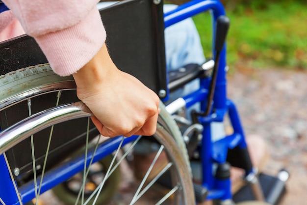 환자 서비스를 기다리는 병원 공원에서 도로에 휠체어 바퀴에 손 핸디캡 여자