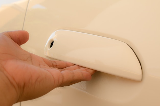Hand on handle. close-up of man in opening a car door