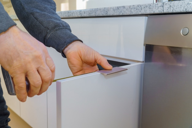 Hand on handle installation door in kitchen cabinet