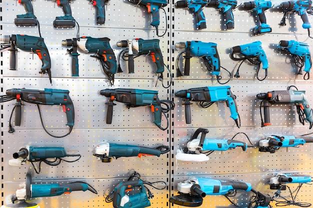 店内のスタンドにあるハンドヘルド電動工具。ハンマードリル、研削盤、電動ドライバー、ワークショップツール