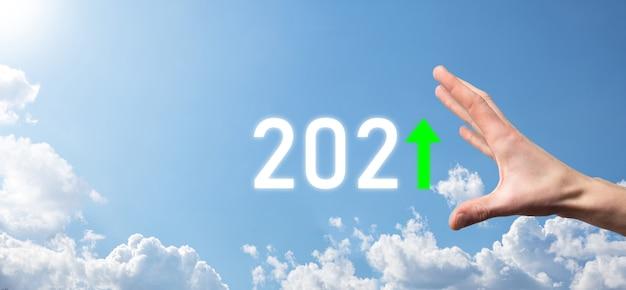 空の背景に2021年のポジティブアイコンを手に持ってください。2021年のコンセプトでビジネスのポジティブな成長を計画します。ビジネスマンの計画と彼のビジネスの肯定的な指標の増加、ビジネスコンセプトの成長。