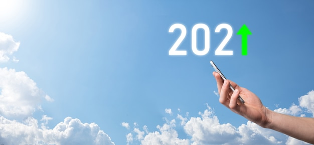 손을 잡고 하늘 배경에 2021 긍정적 인 아이콘 2021 년 개념에서 비즈니스 긍정적 인 성장을 계획하십시오. 사업 계획 및 그의 사업에서 긍정적 인 지표의 증가, 비즈니스 개념 성장.