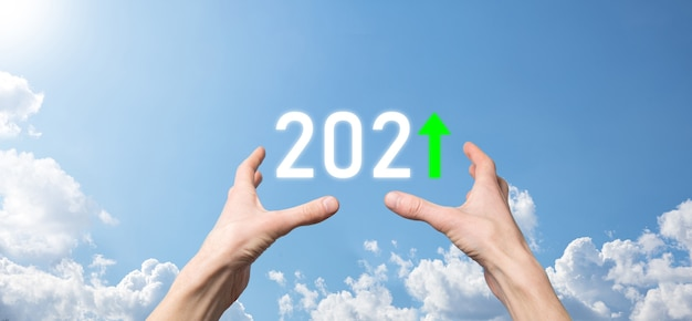 Hand hold 2021 positive icon on sky background.plan business positive growth in year 2021 concept. businessman plan and increase of positive indicators in his business, growing up business concepts.