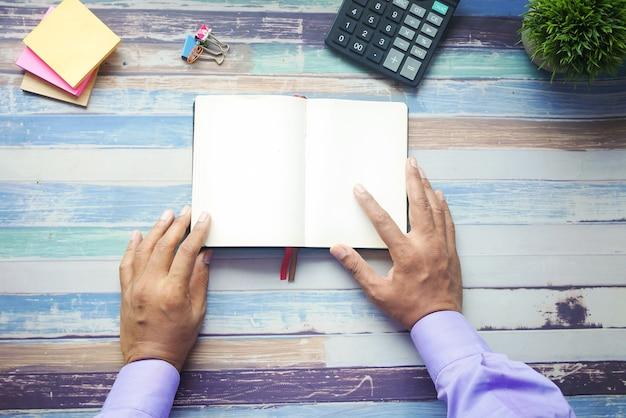 開いた本をテーブルに手で持ってください