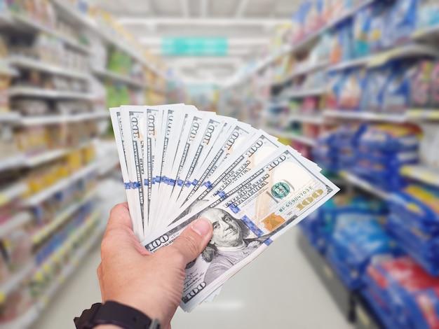 手はショッピングストアで米ドルの米ドル紙幣を保持します。