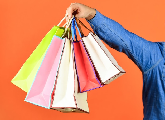 Hand hold bags. shopping bags in hand on red background. paper bags different colors. shopping in mall. black friday concept. holidays preparation and celebration. gift and present. delivery.