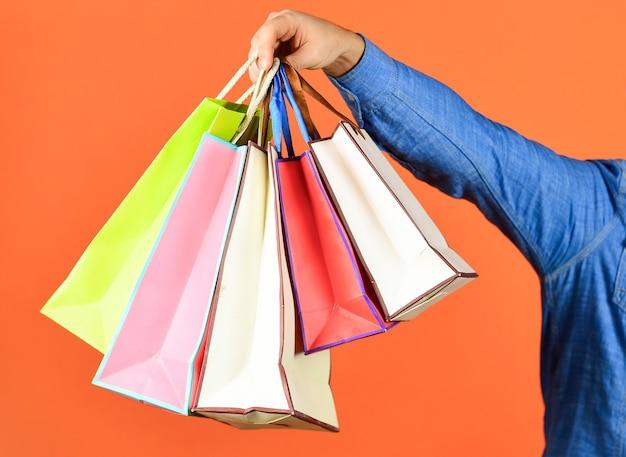 ハンドホールドバッグ。赤い背景に手に買い物袋。色違いの紙袋。モールでの買い物。ブラックフライデーのコンセプト。休日の準備とお祝い。ギフトとプレゼント。配達。