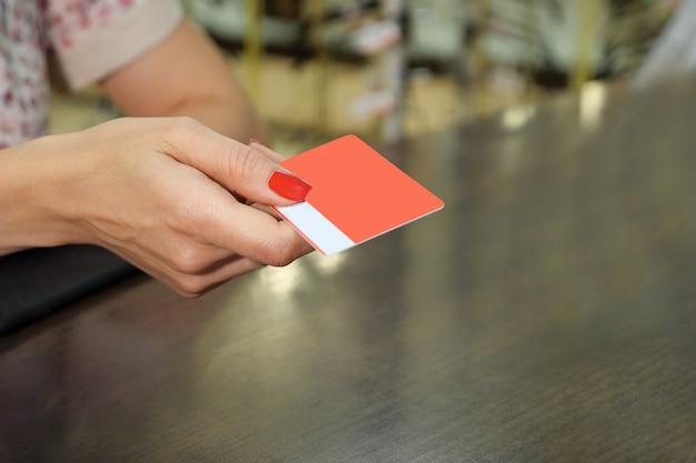 Рука держит пустой красный макет карты лояльности с закругленными углами. простой vip макет шаблона, держащего руку, крупным планом.