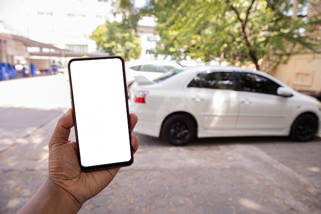 Hand hold blank screen on mobile, cellphone, tablet on blurry white car.