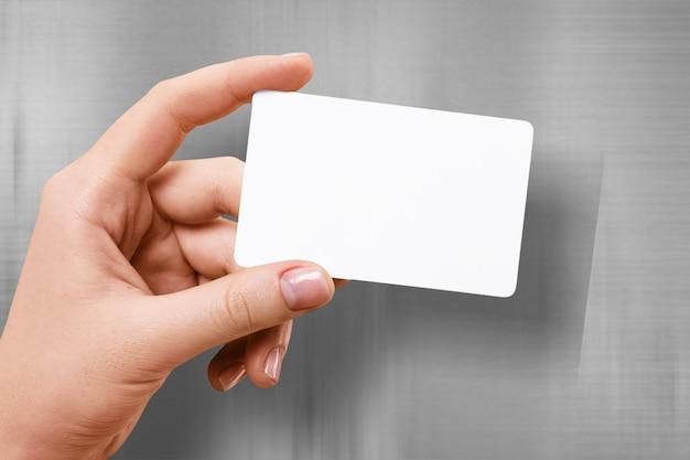 Рука держит пустой полупрозрачный макет карты с закругленными углами.