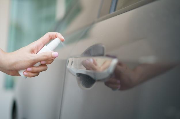 コロナウイルスまたはcovid-19保護のために、車の消毒ドアハンドルにボトルアルコールスプレーをスプレーする手。