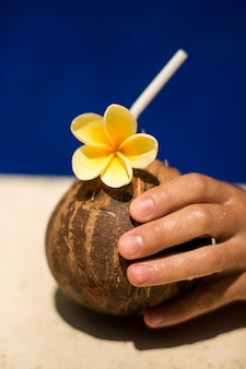 Hand hold coconut drink with yellow flower at poolside