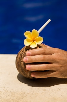 Hand hold coconut drink with yellow flower