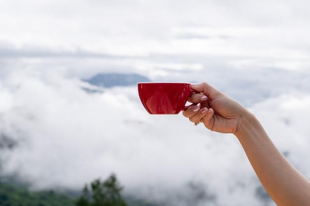 손을 잡고 커피 컵과 아침 해의 커피