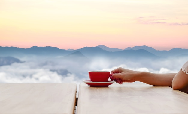 Hand hold coffee cup and coffee of morning sun