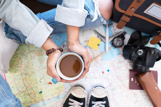 Hand hold coffee and planning for travel