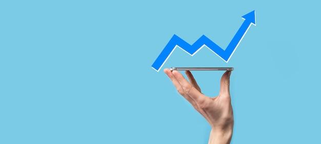 손을 잡고 화면 성장 그래프, 긍정적인 성장 아이콘의 화살표 위쪽 화살표가 있는 창의적인 비즈니스 차트를 가리키는 화살표. 금융, 비즈니스 성장 개념입니다.