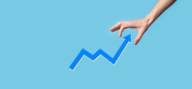 손을 잡고 화면 성장 그래프, 긍정적 인 성장 아이콘의 화살표. 위쪽 화살표와 함께 창조적 인 비즈니스 차트에서 가리키는. 금융, 비즈니스 성장 개념입니다.