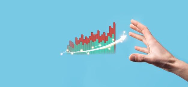 Рука удерживайте рисунок на экране растущего графика, стрелка значка положительного роста. указывая на творческую бизнес-диаграмму со стрелками вверх. концепция финансового, бизнес-роста.