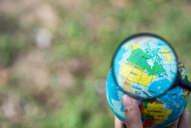 手は地球の地球の球を保持し、アメリカの上に拡大、このイメージの要素は、付属のb