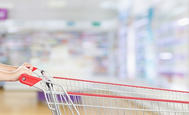 Hand hold empty red shopping cart with pharmacy drugstore blur abstract backbround with medicine and healthcare product on shelves