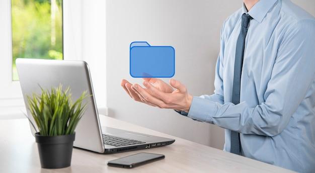 Значок папки в руке. система управления документами или установка dms ит-консультантом с помощью современного компьютера ищут управляющую информацию и корпоративные файлы.