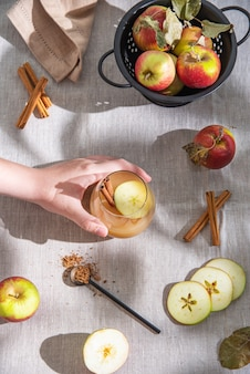 Hand hold a glass of freshly brewed hot apple drink with apple slices and cinnamon on linen tablecloth. top view and flat lay
