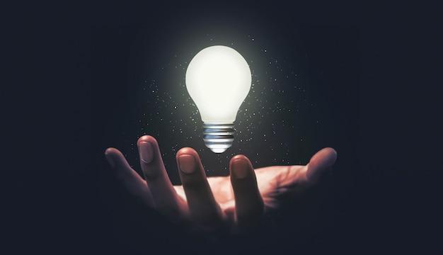 Рука держит светящуюся лампочку идеи и творческую концепцию инновационного мышления на темном фоне вдохновения успеха с творческим бизнес-дизайном решения.