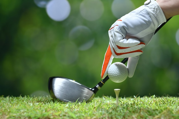 Hand hold golf ball with tee on golf course