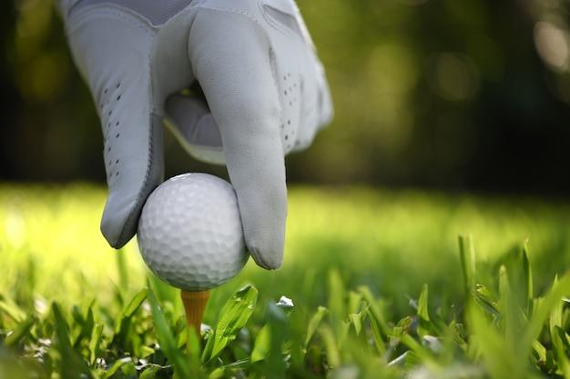 Рука держать мяч для гольфа с тройником на поле для гольфа