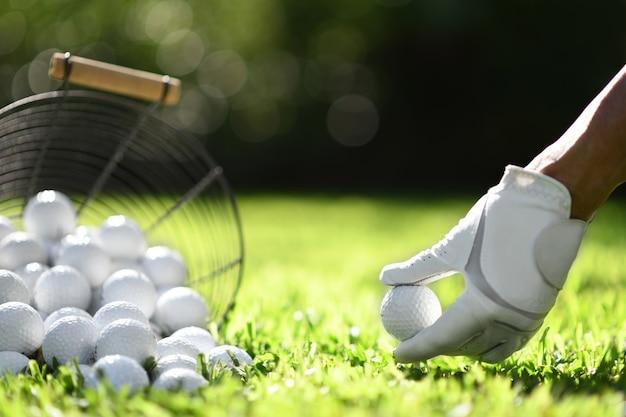 Рука держит мяч для гольфа с тройником на зеленой траве для практики